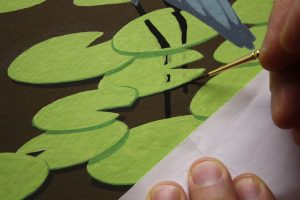 Painting the lily pad shadow. Note the piece of paper used under my brush hand to protect the painting. Gouache is water based paint.