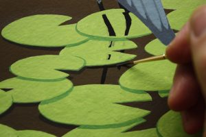 A close-up of me painting the lily pad shadow with my Windsor & Newton Regency Gold 540 #1.